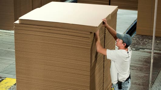 An International Paper Co. employee stacks corrugated boxes at the company's factory in Mt. Carmel, Pennsylvania.
