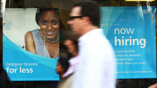 Pedestrians walk by a now hiring sign posted in the window of a Ross Dress for Less store on June 6, 2014 in San Francisco.