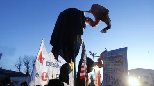 Protesters, holding a mock vulture, rally against layoffs in front of the factory of U.S. automotive supplier Lear on the outskirts of Buenos Aires July 30, 2014. The protesters were also demonstrating against holdout investors locked in a legal battle with Argentina that could trigger a debt default by the country this week.