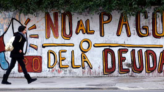 "A woman walks past a graffiti that reads ""No to the debt payment"" in Buenos Aires, July 28, 2014."