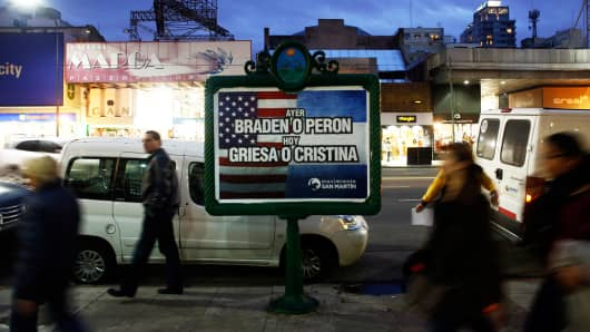 "People walk past a poster that reads ""Yesterday, Braden or Peron - Today: Griesa or Cristina,"" in Buenos Aires, Argentina, July 29, 2014."
