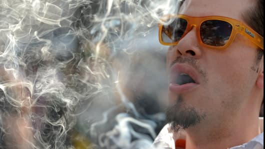 A man smokes a marijuana cigarette during the Colorado 420 Rally at Civic Center Park in Denver, Colo.