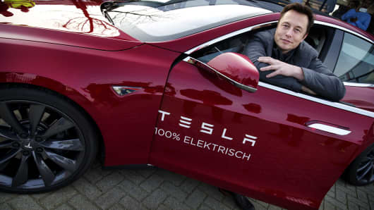 Elon Musk, co-founder and CEO of American electric vehicle manufacturer Tesla Motors, poses with a Tesla during a visit to Amsterdam on January 31, 2014.