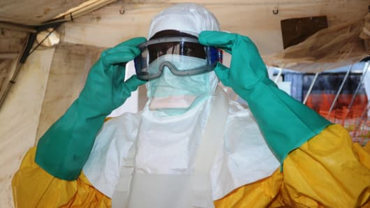 A picture taken on June 28, 2014 shows a member of Doctors Without Borders (MSF) putting on protective gear at the isolation ward of the Donka Hospital in Conakry, where people infected with the Ebola virus are being treated.