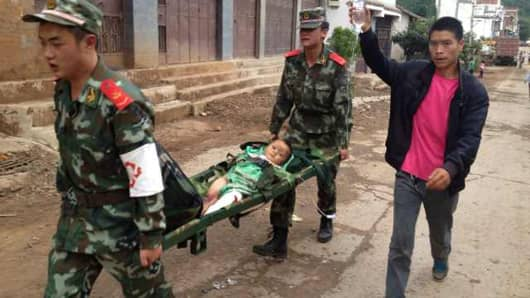 Rescuers carry an injuried child on a stretcher after a 6.1 magnitude earthquake hit the area in Ludian county in Zhaotong, southwest China's Yunnan province.