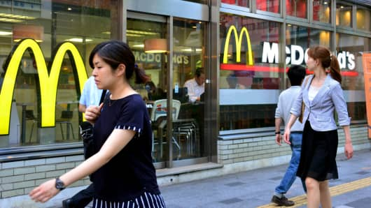 Pedestrians pass before a McDonald's restaurant in Tokyo on July 23, 2014.
