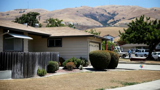 A home with a dead lawn stands in front of hills that are browned with dried grass on July 18, 2014, in Fremont, California.