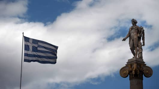 A Greek flag waves next to a statue of the Greek ancient god Apollo in Athens, Greece.