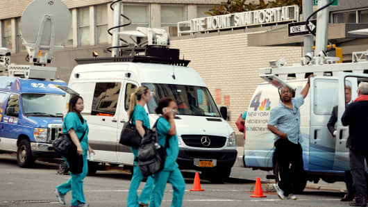 Television trucks outside Mount Sinai Hospital, August 4, 2014, in New York, after officials announced a male patient who recently traveled to West Africa is being tested for the Ebola virus.