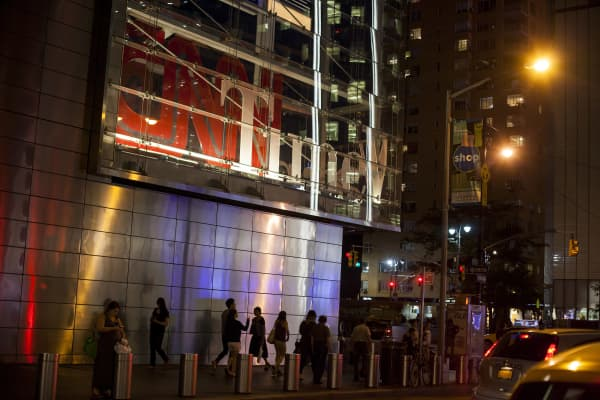 Pedestrians walk past the Time Warner Center in New York. 21st Century Fox withdraws offer for Time Warner on Aug. 5th, 2014.