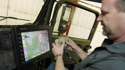 Oshkosh Corporation chief engineer for Unmanned Systems, demonstrates a remote steering device for the TerraMax autonomous vehicle on a test course outside of Pittsburgh, Pennsylvania.