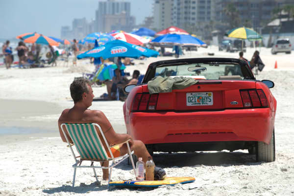 Man sitting by Mustang on Daytona Beach, Florida
