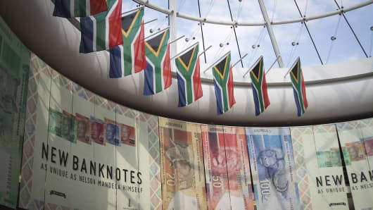 South African national flags hang above an advertisement for the new Mandela rand banknotes at the headquarters of the central bank in Pretoria, South Africa, on May 23, 2013.
