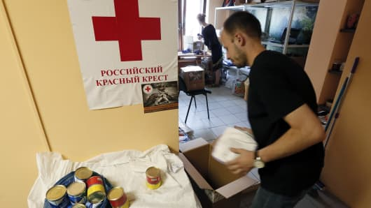 Employees of a small private company sort items to be distributed to victims of the crisis in eastern Ukraine at a collection point in Krasnoyarsk, July 3, 2014. The humanitarian aid is being collected in cooperation with the regional office of the Russian Red Cross.
