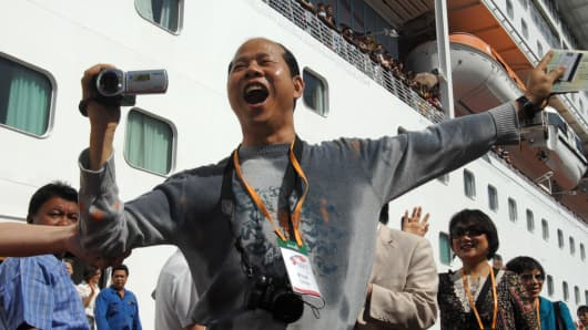 Chinese tourists wave as their passenger ship 'Legend of The Seas' arrives in Taiwan's northern Keelung harbor.