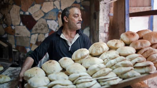 A worker moves a tray of freshly baked bread in a bakery in Cairo, Egypt.