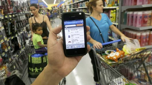 In this Sept. 19, 2013 file photo, a Wal-mart representative demonstrates the now-discontinued Scan & Go mobile application on a smartphone at a Wal-mart store in San Jose, Calif.