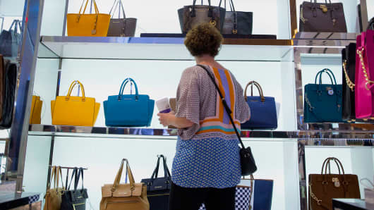 A customer browses Michael Kors handbags at the Macy's flagship store in New York, August 6, 2014.