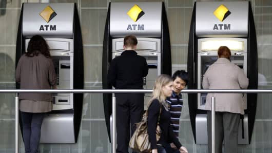 Customers use the automated teller machines (ATM) at a Commonwealth Bank of Australia branch in Sydney, Australia.