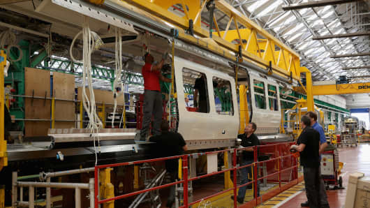 Technicians work on London Underground trains at the Bombardier Transport manufacturing plant in Derby, England