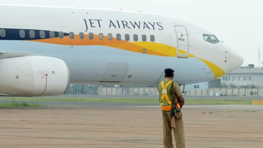 An Indian security official looks on as an aircraft of Jet Airways taxies after landing at Indira Gandhi International Airport in New Delhi, India.