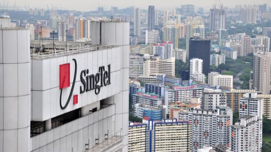 A Singapore Telecom (SingTel) logo is seen on a building overlooking the skyline in Singapore.