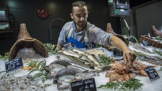 A trader arranges a chilled display of fresh fish on a seafood stall at the Victor Hugo indoor market in Toulouse, France.