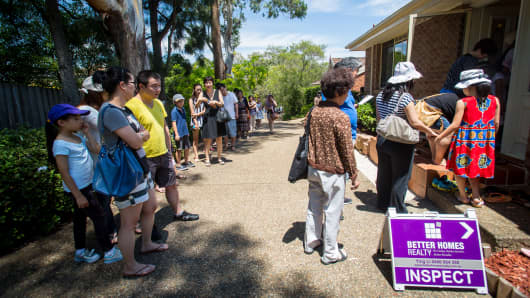 Prospective buyers wait in line to inspect a house for sale in the suburb of Eastwood in Sydney, Australia.