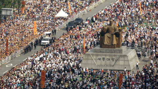 Pope Francis, in a white car, passes a bronze statue of King Sejong, the 15th-century Korean King, as he arrives to attend a beatification mass at Gwanghwamun Square, Seoul.