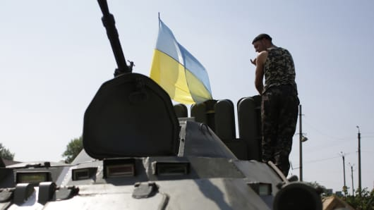 A Ukrainian soldier stands on an armored personnel carrier bearing a flag of Ukraine at a checkpoint near Debaltseve, in the Donetsk region.