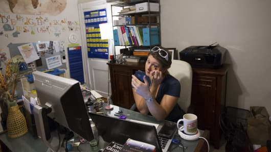 Starting a long day around 4 a.m., Jennifer Guidry, who earns money by offering transportation or services through a variety of apps like Uber, Lyft and TaskRabbit, applies makeup in her home office.
