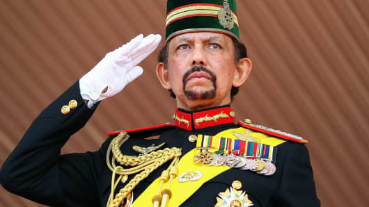 Brunei's Sultan Hassanal Bolkiah salutes during a ceremony to mark his 68th birthday in Bandar Seri Begawan on August 14, 2014.