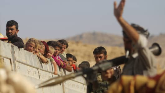 A Yazidi fighter who recently joined the Kurdish People's Protection Units gestures while securing a road in Mount Sinjar, August 13, 2014.
