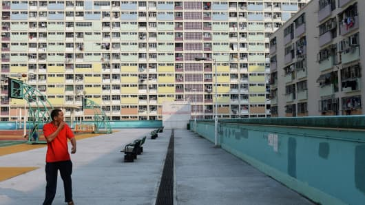A man walks through a residential estate in Hong Kong.