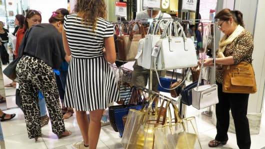 Shoppers looking at Michael Kors bags at Macy's in New York.