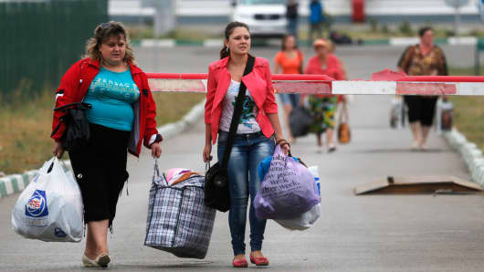 Ukrainian refugees walk from Ukraine into Russia at border crossing point Donetsk, in Russia's Rostov Region, August 19, 2014.