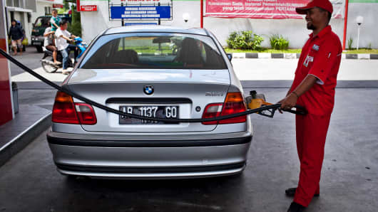 A station attendant refuels a car at a fuel station in Yogyakarta, Indonesia.