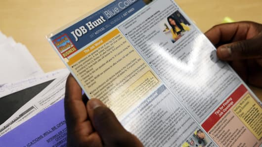 A career counselor reviews a document with information about finding jobs at the Western Addition Neighborhood Access Point in San Francisco.