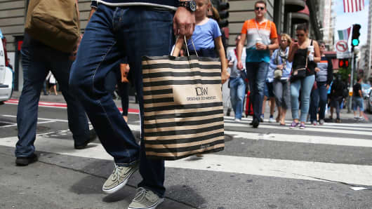 A shopper carries a bag from Designer Shoe Warehouse on August 13, 2014 in San Francisco, Calif.