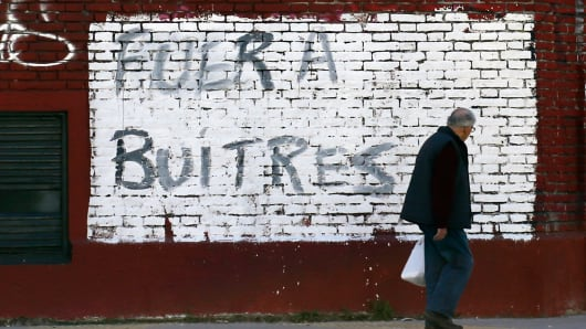"A man walks past graffiti that reads, ""Get out vultures"" in Buenos Aires, August 14, 2014."