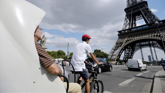 Tourists ride in a pedicab near the Eiffel Tower in Paris.