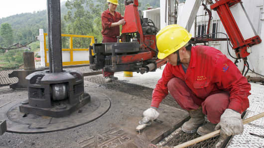 Workers tend to a drill well at an exploration site in the Longgang gas field in Lishan, in southwest China's Sichuan province.