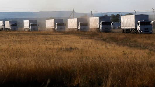 Trucks of a Russian convoy carrying humanitarian aid for Ukraine drive before parking at a camp near Donetsk located in Rostov Region, August 21, 2014.