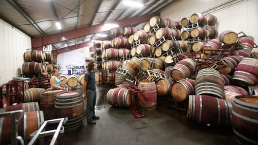 An associate winemaker of Bouchaine Vineyards, surveys fallen wine barrels after a 6.0 earthquake in Napa, California August 24, 2014.