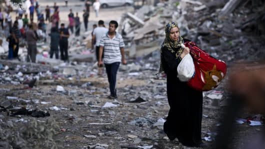 A Palestinian woman takes some of her belongings from her partially destroyed home across the street from where a high rise apartment building in Gaza City was targeted by Israeli airstrikes, Aug. 26, 2014.