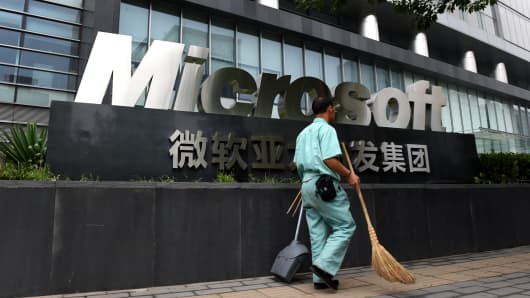 A cleaner walks past a Microsoft sign outside a Microsoft office building in Beijing, China.