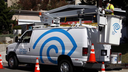 A field technician for Time Warner Cable, prepares to clean and check the connection for a WiFi hotspot using a bucket truck in Manhattan Beach, California.