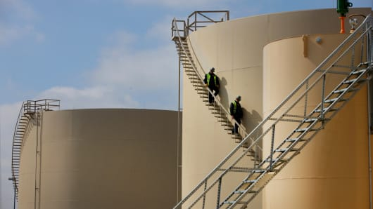 Workers on the stairs of an oil storage tank at the Musket Corp. Windsor Crude Terminal in Windsor, Colorado.