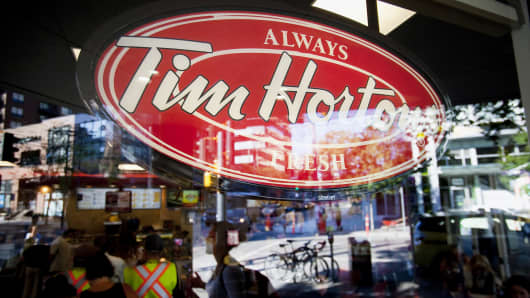 Tim Hortons signage is displayed in the window of a restaurant in downtown Vancouver, British Columbia, Canada, on Tuesday, Aug. 26, 2014.