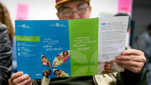 A man reads a pamphlet from Maryland's Obamacare exchange while waiting to speak to a health navigator in Silver Spring, Md., Saturday, Dec. 7, 2013.